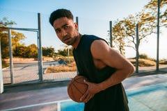 Hombre negro que juega al baloncesto, bola de la calle, hombre que juega, competencias de deporte, afro, retrato al aire libre, j Imagenes de archivo