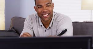 Hombre negro que mueve de un tirón a través de los canales en la TV Fotos de archivo libres de regalías
