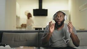 Hombre negro que pone los auriculares en la cocina abierta Individuo sonriente que hace el movimiento de la danza almacen de video