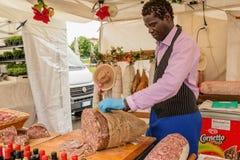 Hombre negro que prepara la salchicha en el mercado Fotos de archivo libres de regalías
