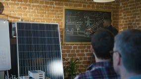 Hombre negro que presenta la batería solar moderna almacen de metraje de vídeo