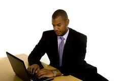 Hombre negro que pulsa en la computadora portátil Foto de archivo libre de regalías