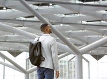 Hombre negro que se coloca solamente en aeropuerto con el bolso foto de archivo libre de regalías