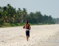 Hombre negro que se ejecuta en la playa Imagen de archivo libre de regalías