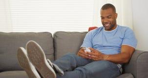 Hombre negro que se sienta en mandar un SMS del sofá foto de archivo