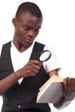 Hombre negro que sostiene una lupa Imagen de archivo