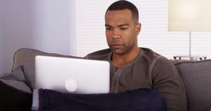 Hombre negro que usa el ordenador portátil en el sofá fotografía de archivo
