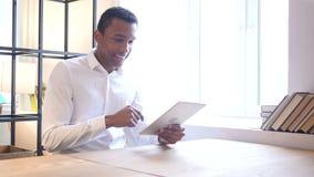 Hombre negro que usa la tableta en oficina metrajes