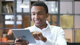 Hombre negro que usa la tableta en oficina almacen de metraje de vídeo