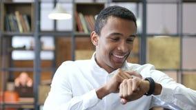 Hombre negro que usa Smartwatch en oficina almacen de video