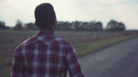Hombre negro que va derecho camino del campo