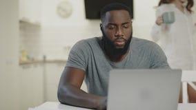 Hombre negro serio que trabaja en el ordenador portátil en la cocina abierta T? de consumici?n sonriente de los pares almacen de metraje de vídeo