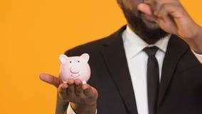 Hombre negro sonriente en el traje que pone monedas en ahorros de la inversi?n de capitales de la hucha almacen de video