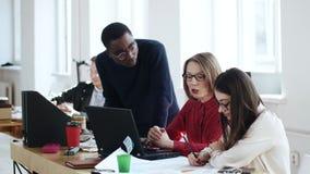 Hombre negro sonriente joven feliz del encargado que coopera con dos colegas femeninos de la edad diversa en la oficina de moda m almacen de metraje de vídeo