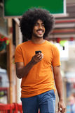 Hombre negro sonriente que camina con el teléfono móvil Fotos de archivo libres de regalías