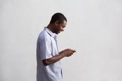 Hombre negro sonriente que camina y que usa el teléfono móvil Imagen de archivo