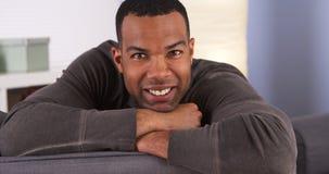Hombre negro sonriente que descansa sobre el sofá Imagenes de archivo