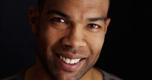 Hombre negro sonriente que mira la cámara Foto de archivo