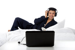 Hombre nepalés joven en pijamas, computadora portátil. Imagen de archivo libre de regalías