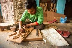 Hombre nepalés no identificado que trabaja en su taller de madera, el 19 de diciembre de 2013 en Bhaktapur, Nepal Foto de archivo
