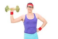 Hombre Nerdy que levanta una pesa de gimnasia del bróculi Imagenes de archivo