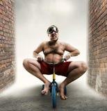 Hombre Nerdy que monta una pequeña bicicleta Foto de archivo libre de regalías