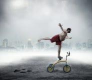Hombre Nerdy que se coloca en una pequeña bicicleta Fotos de archivo