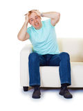Hombre nervioso de la histeria en el país en el sofá imagenes de archivo