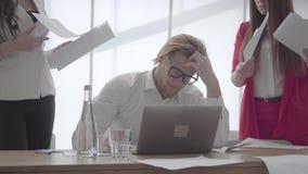 Hombre nervioso del retrato que se sienta en oficina moderna con netbook en la tabla que recoge los documentos que dos colegas fe metrajes