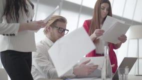 Hombre nervioso del retrato que se sienta en oficina moderna con netbook en la tabla que recoge los documentos que dos colegas fe almacen de metraje de vídeo
