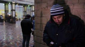 Hombre nervioso que sostiene un paquete en su mano y que espera alguien Criminal metrajes