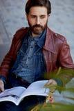 Hombre nive atractivo que lee una revista en política y finanzas en la terraza del verano Imagen de archivo