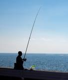 Hombre no identificado con la caña de pescar cerca de la costa del océano en día soleado fotos de archivo libres de regalías