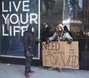 Hombre no identificado con la muestra que pide dinero comprar la mala hierba en Broadway durante semana del Super Bowl XLVIII en M Foto de archivo libre de regalías