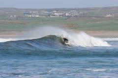 Hombre no identificado que practica surf las ondas Fotos de archivo libres de regalías