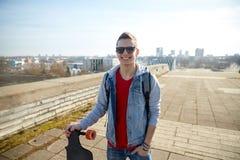 Hombre o adolescente sonriente con longboard en la calle Fotos de archivo libres de regalías