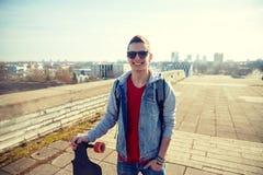 Hombre o adolescente sonriente con longboard en la calle Fotografía de archivo