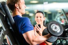 Instructor personal en gimnasio y el entrenamiento de la pesa de gimnasia Fotografía de archivo libre de regalías