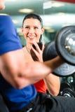 Instructor personal en gimnasio y el entrenamiento de la pesa de gimnasia Foto de archivo libre de regalías
