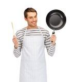 Hombre o cocinero feliz en delantal con la cacerola y la cuchara imagen de archivo