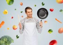 Hombre o cocinero feliz en delantal con la cacerola y la cuchara fotos de archivo libres de regalías