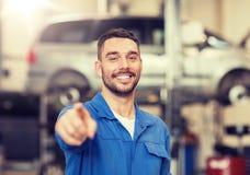 Hombre o forjador feliz del mecánico de automóviles en el taller del coche fotos de archivo libres de regalías