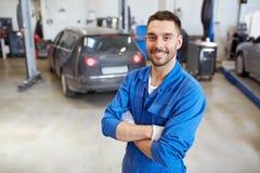 Hombre o forjador feliz del mecánico de automóviles en el taller del coche imagenes de archivo