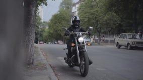 Hombre o mujer que lleva un equipo de la motocicleta que monta una motocicleta del motorista a lo largo de un camino de ciudad Mo metrajes