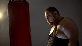 Hombre obeso con la agresión que mira proyección de imagen del saco de arena su opositor, caja imágenes de archivo libres de regalías