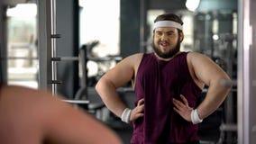 Hombre obeso divertido que mira la reflexión de espejo y que presenta como el machista, motivación imagen de archivo