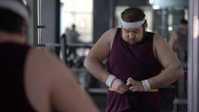 Hombre obeso divertido que se sostiene la cintura de medición del estómago con la cinta, pareciendo satisfecha almacen de video