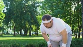 Hombre obeso que corre en parque de la ciudad, superando la holgazanería y la inseguridad, persistentes almacen de metraje de vídeo