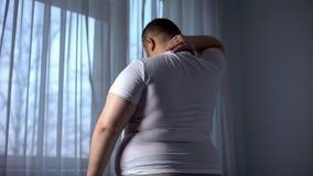 Hombre obeso que estira los músculos del cuello, espalda problemas del dolor causados por el exceso de peso imagenes de archivo
