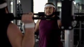 Hombre obeso que hace apenas el ejercicio con el barbell en gimnasio, entrenamiento de la aptitud, deporte imagen de archivo